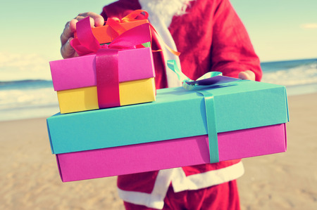 santa claus carrying a pile of gifts on the beach photo