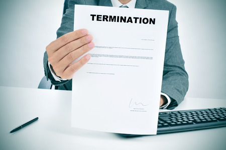 unemployed dismissed: a man in suit in his desk showing a figured signed termination document Stock Photo