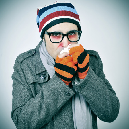 cold season: a man with a cold bundled up in a coat, knit cap, gloves and scarf Stock Photo