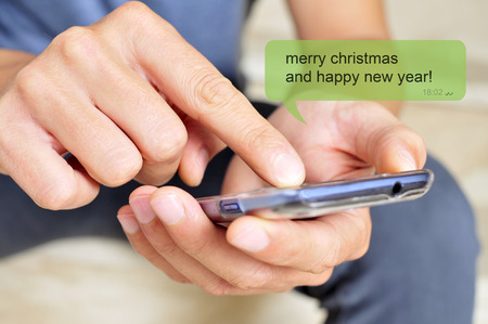 a young man with a smartphone and the text message merry christmas and happy new year in a chat bubble photo