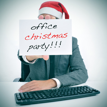 christmas party: a man sitting in his desk with a santa hat holding a signboard with the text office christmas party written in it