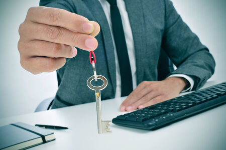 lessee: a man in suit sitting in an office desk giving the key to the observer Stock Photo