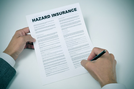 homeowners: closeup of a young man signing a hazard insurance policy