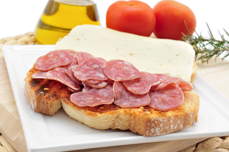 longaniza: closeup of pa amb tomaquet amb fuet, bread with tomato and a typical sausage of Catalonia, Spain Stock Photo