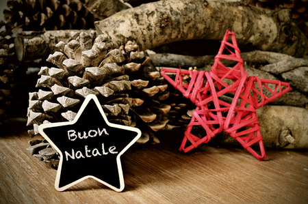 buon: the text buon natale, merry christmas written in italian in a star-shaped blackboard, and a christmas star, some pinecones and a pile of logs in the background Stock Photo