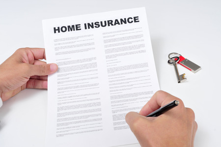 home insurance: closeup of a young man signing a home insurance policy
