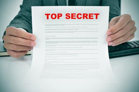 Een man draagt een pak met een document onder leiding van de woorden top secret Stockfoto