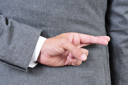 deceive: a man wearing a suit crossing his fingers in his back Stock Photo