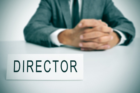 a man in suit sitting in a desk with a nameplate in front of him with the word director written in it photo