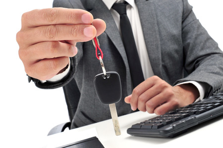 courtesy: a man in suit sitting in an office desk giving a car key to the observer Stock Photo