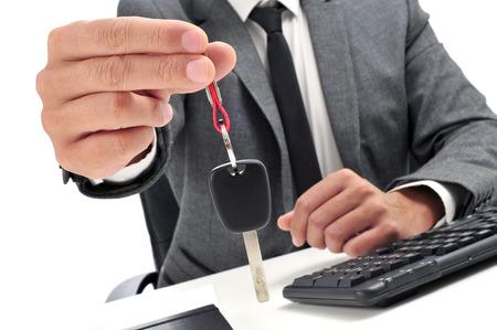 een man in pak zitten in een kantoor bureau het geven van een autosleutel aan de waarnemer