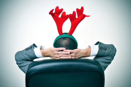 Un homme avec un bois de renne bandeau de détente dans son fauteuil de bureau après un bureau fête de noël