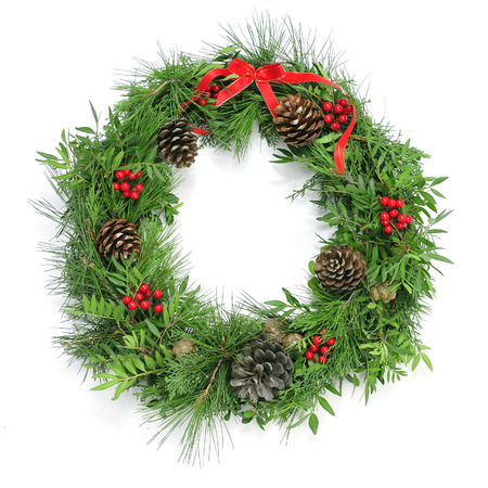 a natural christmas wreath with pine cones berries and a red ribbon bow on a