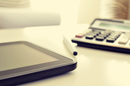 freelance: closeup of a desk with a tablet and a calculator in an office with a nice atmosphere Stock Photo