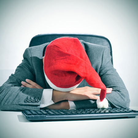 after the party: a man in suit with a santa hat sleeping in his desk after an office christmas party
