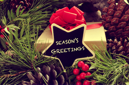 festive pine cones: a star-shaped signboard with the text seasons greetings written in it, with a gift and some natural ornaments such pine cones and red berries in the background