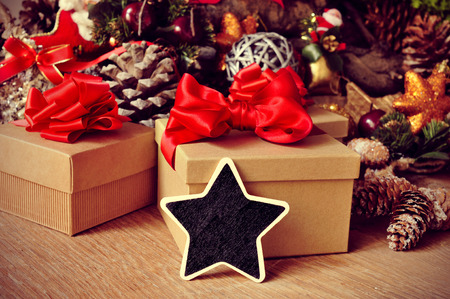 a blank star-shaped chalkboard on a rustic wooden table full of gifts and christmas ornaments, such christmas stars and pine cones photo