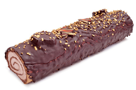 yule log: a yule log cake, traditional of christmas time, on a white background