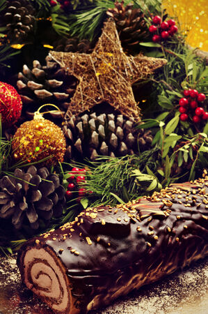 festive pine cones: closeup of a yule log cake, traditional of christmas time, on a table ornamented with christmas balls and satrs, and natural ornaments