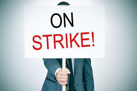 a young man in suit with a protest signboard with the text on strike written in it