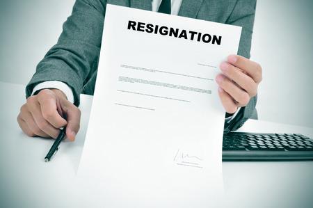 un homme en costume dans son bureau montrant un document de démission signé compris Banque d'images