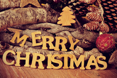 fireplace christmas: wooden letters forming the sentence merry christmas on a rustic wooden table with logs and pine cones in the background