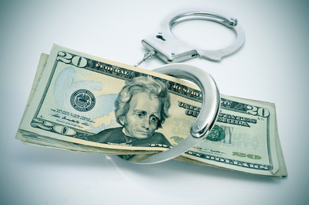 mafioso: a pair of handcuffs and some dollar bills depicting the idea of arrest for bribery or corruption
