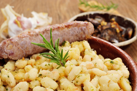 llonganissa: closeup of an earthenware bowl with botifarra amb mongetes, fried white beans and sausage typical of Catalonia, Spain Stock Photo