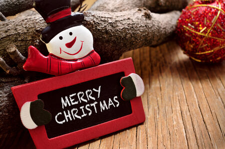 log on: the sentence merry christmas written in a chalkboard in the the shape of a snowman on a rustic wooden surface Stock Photo