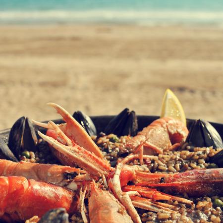 une paella aux fruits de mer typiquement espagnol dans un paellera, le poêle à paella, sur la plage, avec un effet rétro