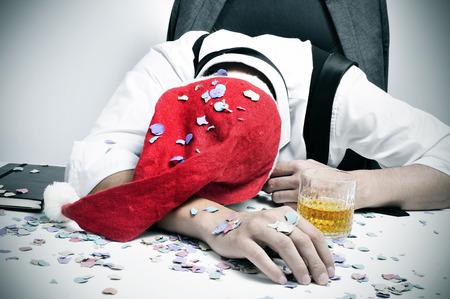 een man met een kerstmuts en bedekt met confetti slapen in zijn bureau na een kantoor christmas party