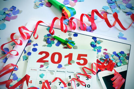 a tablet with a picture of a 2015 calendar on an office desk full of confetti, streamers and a party horn, on an office desk full of confetti, streamers and a party horn photo
