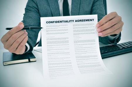 mladý muž ukazuje dohodu utajení dokumentu