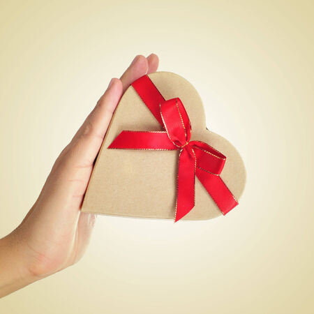a heart-shaped gift box tied with a red ribbon in the hand of a man photo