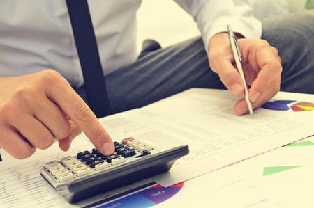 Primer plano de un joven hombre de cheques cuentas con una calculadora Foto de archivo - 34614322