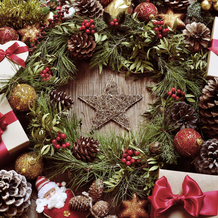 festive pine cones: a rustic wooden table full of gifts, and christmas ornaments, such as a natural wreath with branches, berries and pine cones, or christmas balls and stars , with a retro effect Stock Photo