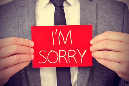 i am sorry: a young man showing a red signboard with the text I am sorry written in it