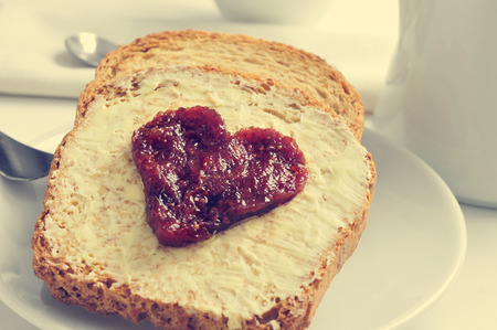 breakfast cup: jam forming a heart on a toast, on a set table for breakfast Stock Photo