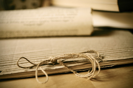 inheritance: detail of an old notepad and some old rolled papers on a wooden table