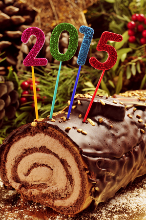 yule log: a yule log cake, traditional of christmas time, with glittering numbers of different colors forming the number 2015, as the new year