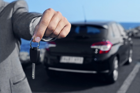 a man in a gray suit offering a car key to the observer, with a car in the background Stockfoto