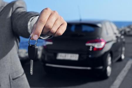 een man in een grijs pak met een autosleutel voor de waarnemer, met een auto op de achtergrond Stockfoto
