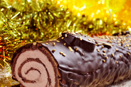 yule log: a yule log cake, traditional of christmas time, on a festive table ornamented with shiny tinsel