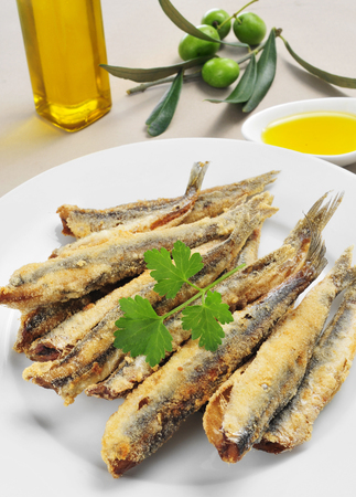 engraulis encrasicolus: closeup of a plate with spanish boquerones fritos, battered and fried anchovies typical in Spain