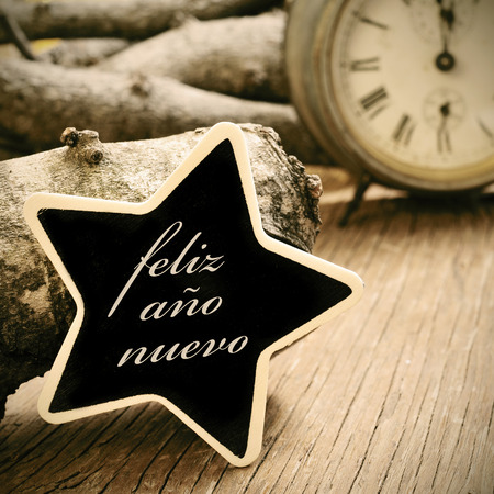 ano: the sentence feliz ano nuevo, happy new year in spanish, written in a star-shaped chalkboard, on a rustic wooden surface, with an old watch in the background, in sepia tone