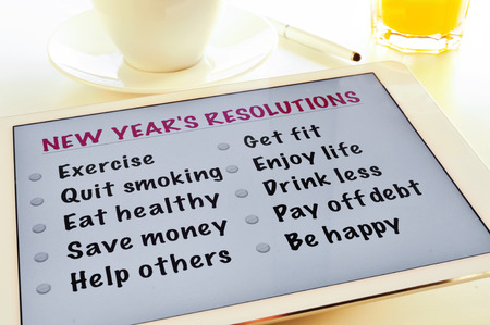 get help: a list of new years resolutions in a tablet, on a table with a cup of coffee and a glass with orange juice Stock Photo