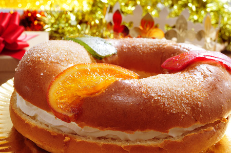 a roscon de reyes, spanish three kings cake eaten on epiphany day, on an ornamented table with gifts and tinsel