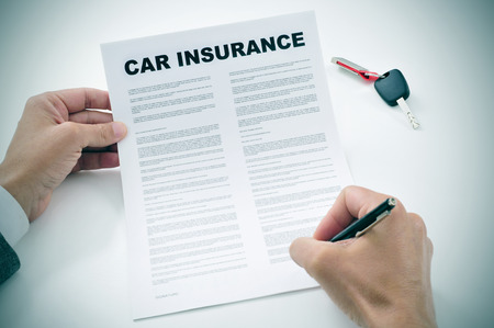 closeup of a young man signing a car insurance policy Stockfoto