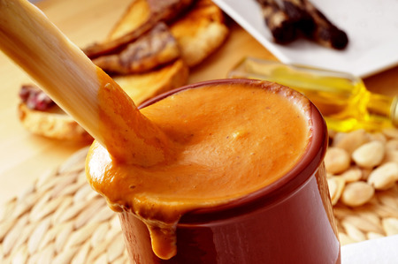 calsots: closeup of a barbecued calcot, sweet onion, dipped in a bowl with romesco sauce, typical of Catalonia, Spain Stock Photo