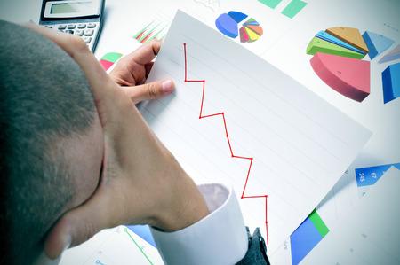 preocupacion: hombre de negocios en su escritorio de la oficina llena de gráficos y tablas de Observación preocupaba un gráfico con una tendencia a la baja